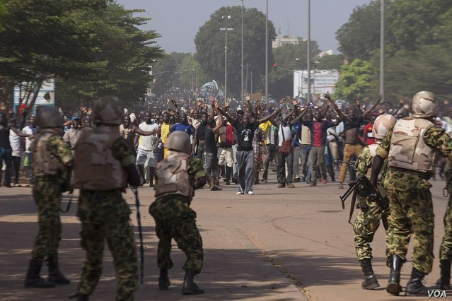 1024px-Soldiers_attempt_to_stop_protesters_from_entering_the_parliament_building_in_Ouagadougou,_Oct._30,_2014.jpg
